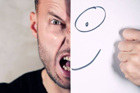 screaming man covers half face with painted smile, close up Stok Fotoğraf