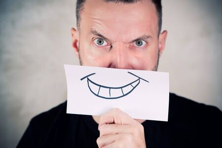 angry man covers his mouth with a sheet with a painted smile. close up
