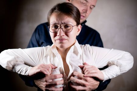 a man tries to use violence against a woman, demonstrating dominance. Woman trying to remove male hands from her chest