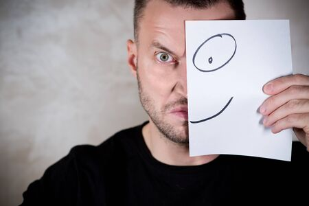 angry man covers half his face with a piece of paper with a painted smile. copy space