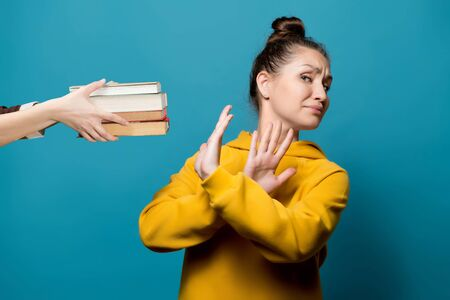 girl refuses books, which a female hand holds out to her, close up, blue background