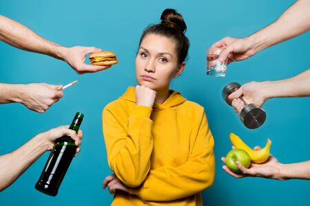 girl reflects on a choice while healthy and not healthy things are offered to her from different sides