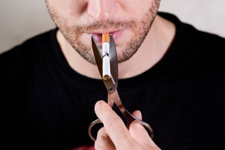 lower half of an unshaven man's face with a cigarette and scissors, close up
