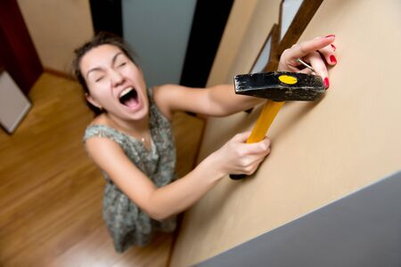 young woman screams, hitting a finger with a hammer, falling past a nail