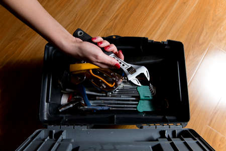 girl with red manicure takes an adjustable wrench from a tool box, top view Stock fotó