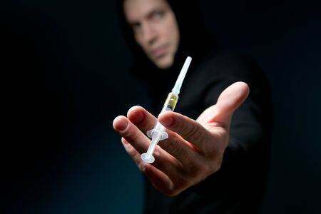 man looks out of the darkness holding out a syringe with a drug, selective focus