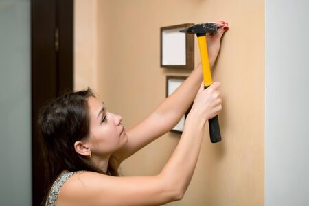 Girl hammer a nail into the wall to hang a photo frame, side view