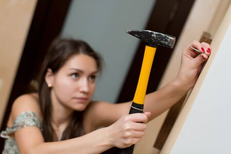 Girl is going to hammer a nail into the wall for photo frames, selective focus