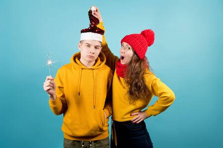 a sad brother with a sparkler in his hand does not express emotions, and his sister is very happy about the Christmas holiday