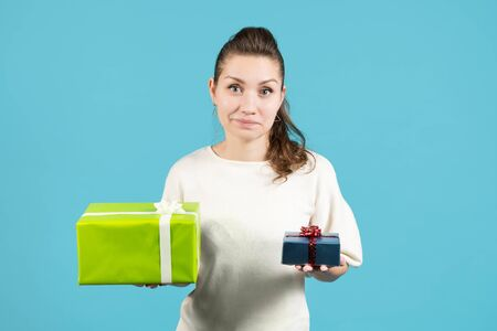 the girl holds in front of her hands a large and small gift, grinning and looking at the camera