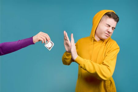A teenager refuses a condom, which is held out by a female hand. Isolated on blue background.
