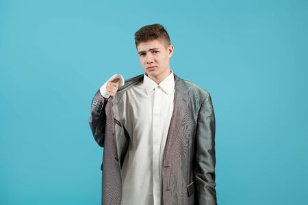 the shirt and jacket of an adult on a young guy look ridiculous. Young man showing, that his clothes is too big for him Reklamní fotografie