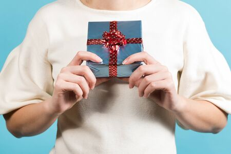 Girl holds a gift near her chest. No face, blue background Foto de archivo