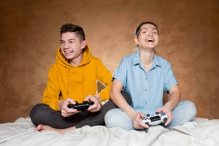 A guy with a girl laughs, holding modified joysticks without identification marks from the game console in their hands