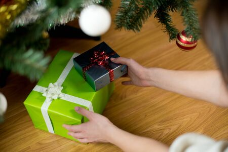 hands reach for gifts under the Christmas tree. Without face 版權商用圖片