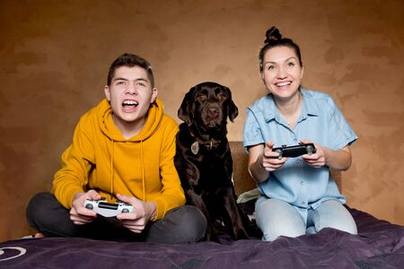 Brother, sister and domestic dog in front of a screen at a computer game. The guys are playing, and the dog is watching