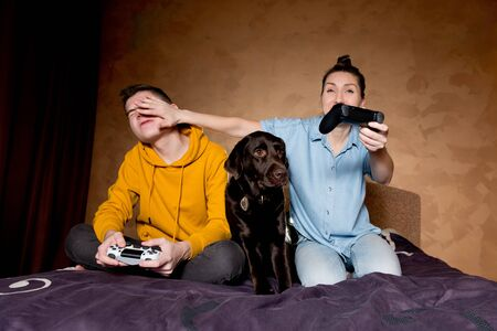 A girl applies a trick in a game with a guy, a dog sits next to them. The guys play the game using modified joysticks without identification marks.