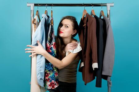 Young woman separates weekend and business clothes, preferring weekend, Blue background Banco de Imagens