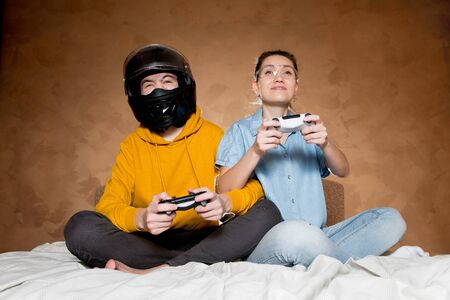 Brother and sister play a computer game with modified joysticks without identification marks. A guy in a motorcycle helmet, a girl with glasses