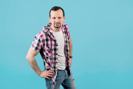 a young man in a plaid shirt, with stubble, looks straight with his hands on his hips and squinting, trying to see something, but his poor eyesight does not allow him to do this