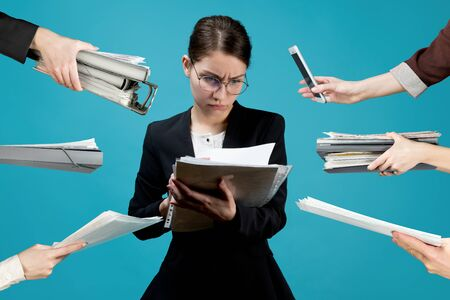 A young business woman in a strict suit carefully scans documents, at this time many hands hold out folders with files and various documents to her Imagens