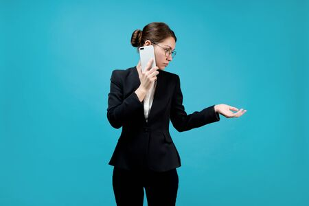 Business young woman in a business suit speaks on the phone and holds out her hand to the side as if taking documents 版權商用圖片