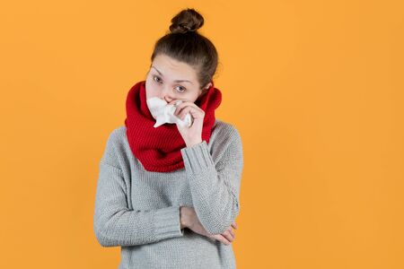 sickly-looking girl in a scarf holds a napkin near her nose and looks at the camera on a yellow background