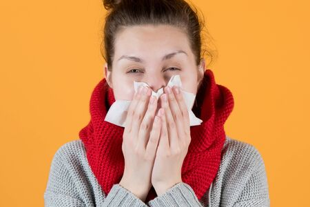 a sickly-looking girl in a scarf squints, sneezing into a scarf on yellow background