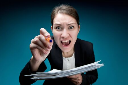 a woman in an office suit with a strict haircut screams into the camera, pokes with a pen and waving documents. Blue background