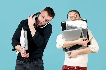 the guy and the girl are very busy with paper office work, they are as a symbol of recycling, congestion. A man speaks on two phones at once, and a woman hugs a bunch of documents