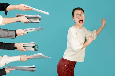 A girl runs from a lot of work that is held out by hands. Office employee trying to escape from a heavy load at work