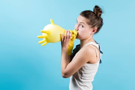Side view of a young woman in a T-shirt inflates a yellow household glove and looks at the camera. Isolated on blue background. Banco de Imagens