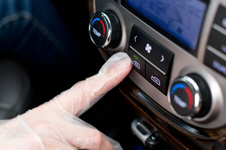 a hand in a medical glove presses the air recirculation button in the car, closing itself from outside air from the street