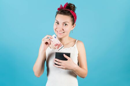 A young woman happily puts or takes out of a box for savings a new bill of ten euros on a blue background