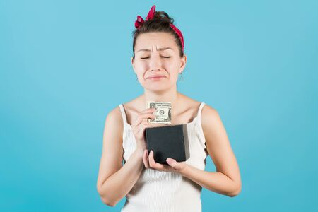 Girl bitterly takes out dollar savings from the savings box on a blue background
