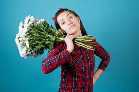 Country girl in a red checkered shirt holds on his shoulder a bouquet of white chrysanthemums on a blue background