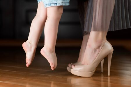 A little girl with bare feet reaches for a shod mom in the hallway at home. Mom takes the baby and the girl comes off the floor. Mom leaves for work or leaves family and home. Close up