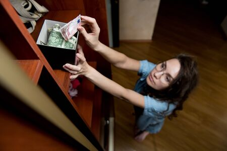 A girl puts or takes dollars from a money-box on the top shelf of a closet. Selective focus on the piggy bank, top view.