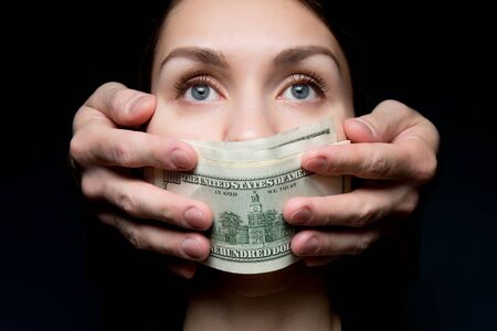 The mouth of a young woman is closed by a stack of dollar bills. Buying silence, a woman looks into the void