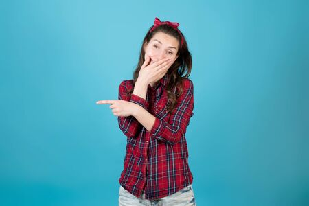 A country girl in a red plaid shirt laughs, covering her mouth and points a finger to the side. Isolated on blue background.