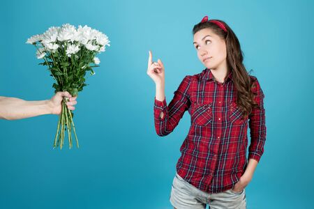 A country girl in a red plaid shirt looks coldly to the side and shows the middle finger - fuck to flowers, a man holds out white chrysanthemums to a girl