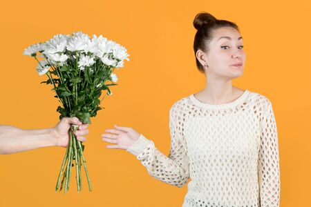 The girl smiles slyly and accepts a gift from a man in the form of flowers - white chrysanthemums. Flowers from a man. Isolated on a yellow background