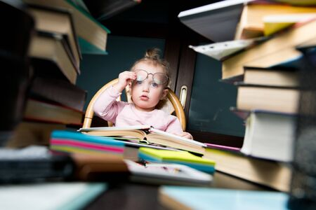 Little girl raises adult glasses for vision. There are a lot of books and educational materials around. The concept of children's learning, the complexity of learning Banco de Imagens