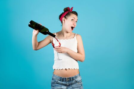 Cheerful bright girl pours the rest of the wine into a large glass on a blue background