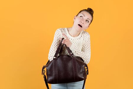 girl diligently looking for something in her purse, looking up, isolated on orange-yellow Imagens