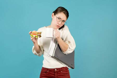 disgruntled girl trying to eat a sandwich while holding coffee, documents and phone. Blue background