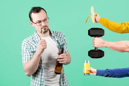 A man lights a cigarette with a bottle of beer in his hand, and at this time he is offered healthy food and sports. smoky man holding banana, juice and dumbbell 版權商用圖片