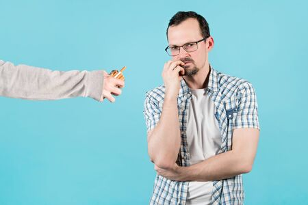 A hand holds out cigarettes to a man who is nervous and bites his nails from excitement or nicotine breaking