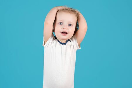 Cute curly baby girl of two years raises her hands up and holds on to her head. Isolated on a blue background