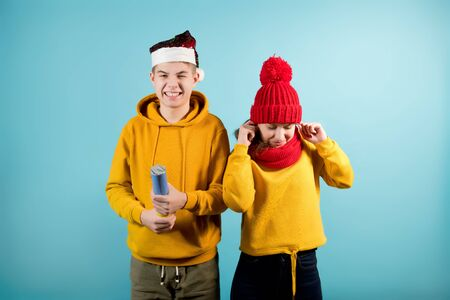 a teenager is about to blow up a cracker with confetti, and his sister is scared nearby, covering her ears with her fingers. Blue background, brother and sister in yellow sweatshirts. one is blow cracker and one is afraid